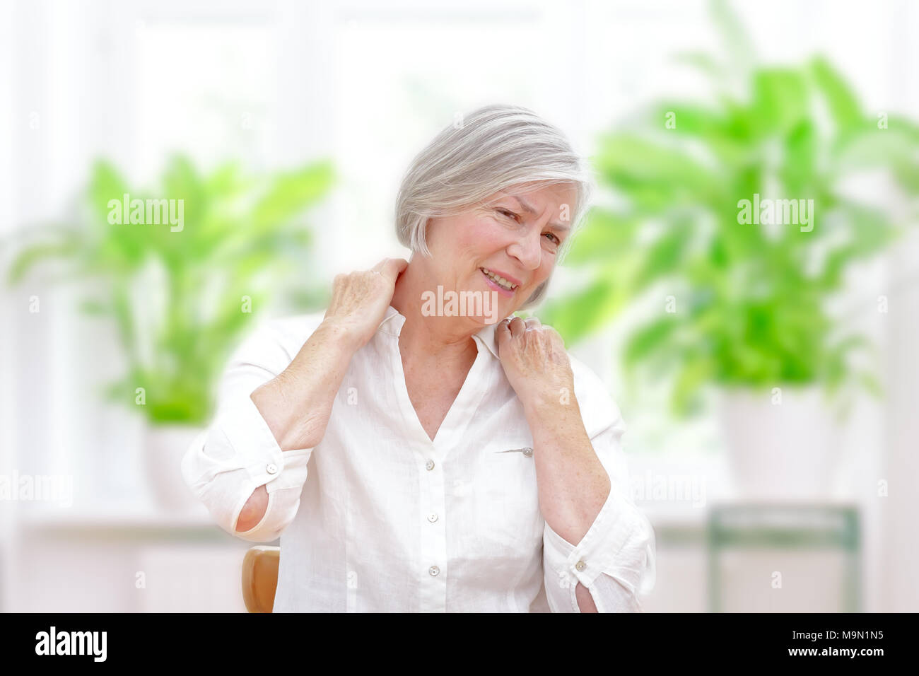 Elderly woman with chronic pain syndrome fibromyalgia suffering from acute shoulder pain - Stock Image