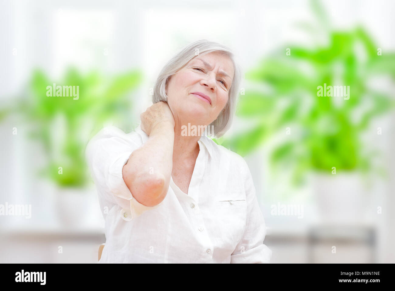 Senior woman with chronic pain syndrome fibromyalgia suffering from acute neckaches - Stock Image