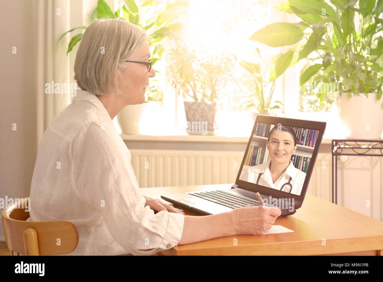 Senior woman in her sunny living room in front of a laptop making notes during a video call with her female doctor - Stock Image