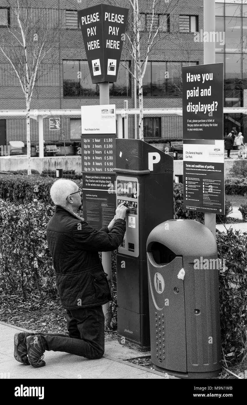 A man struggles to pay for hospital car parking - Stock Image