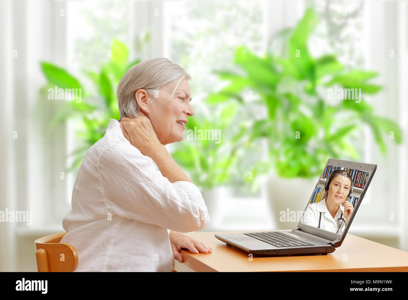 Senior woman in her living room in front of a laptop making a video call with a specialist in orthopedics - Stock Image