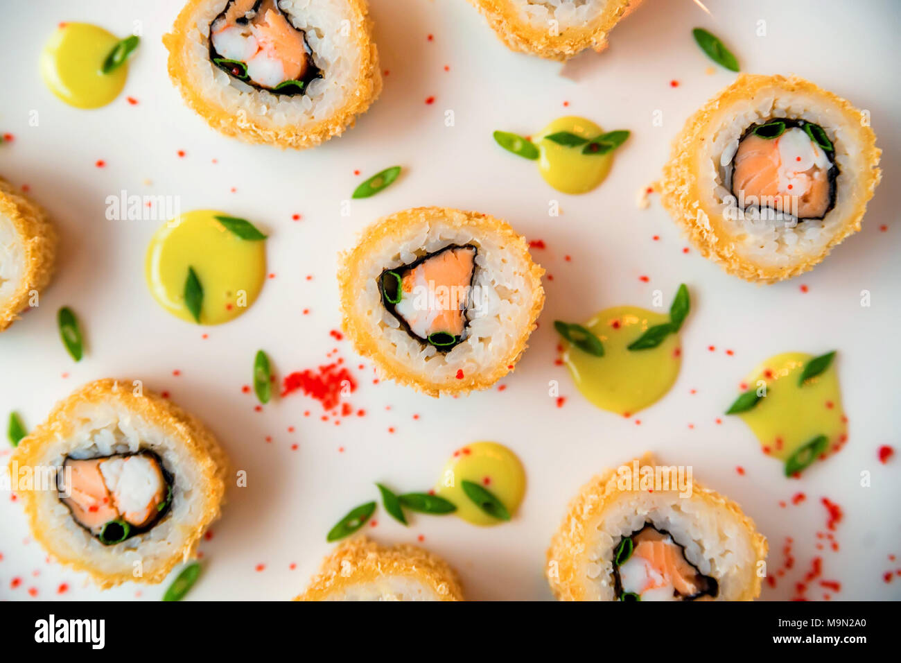 Sushi rolls scattered on white background - Stock Image