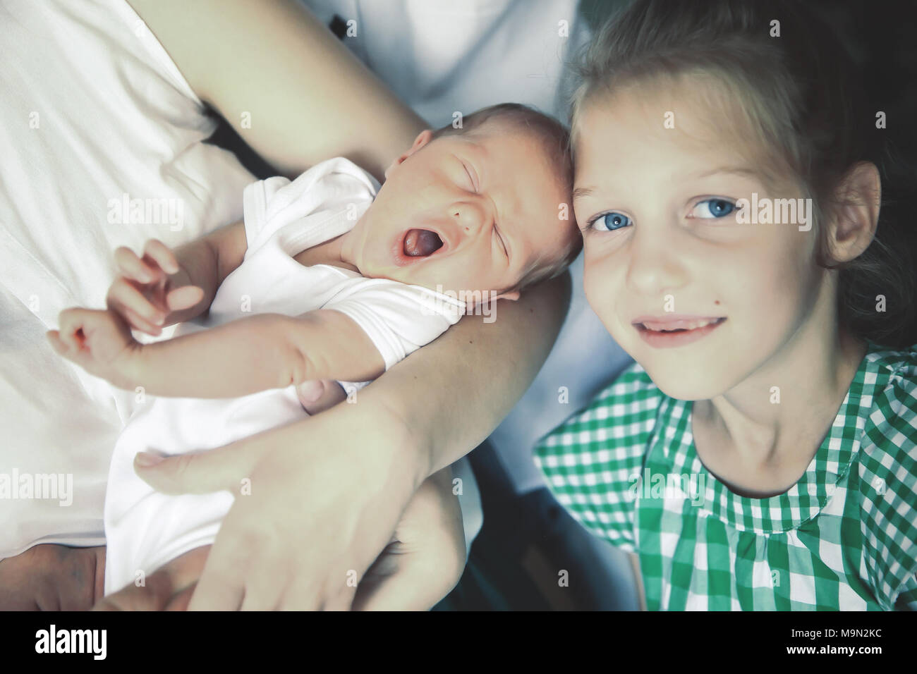 older sister next to a newborn baby - Stock Image