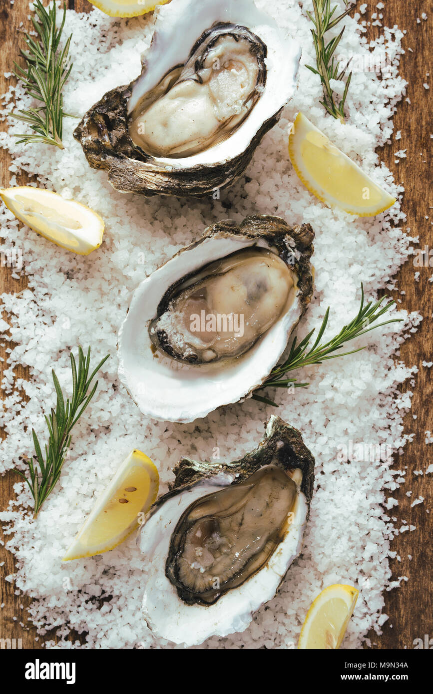 fresh just opened oysters and slice of lemon on rustic wooden background Stock Photo