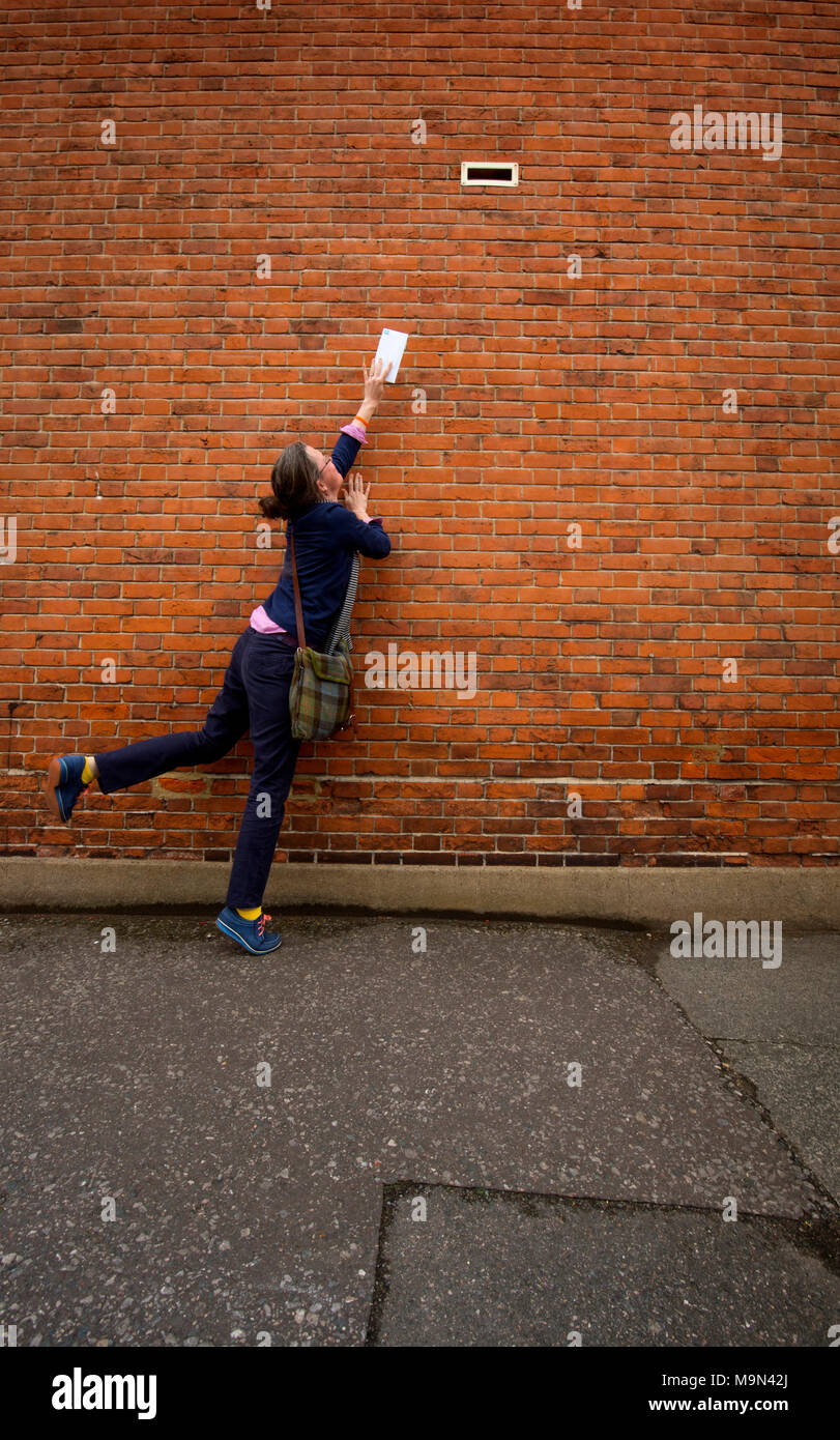 A young woman stretches for a very high up letterbox on a house in Rochester, Kent. - Stock Image