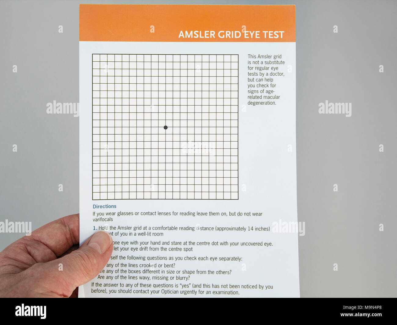 Senior elderly person hand holding and looking at an Amsler Grid Eye Test card to check eyesight for Age-Related Macular Degeneration in eyes. UK - Stock Image