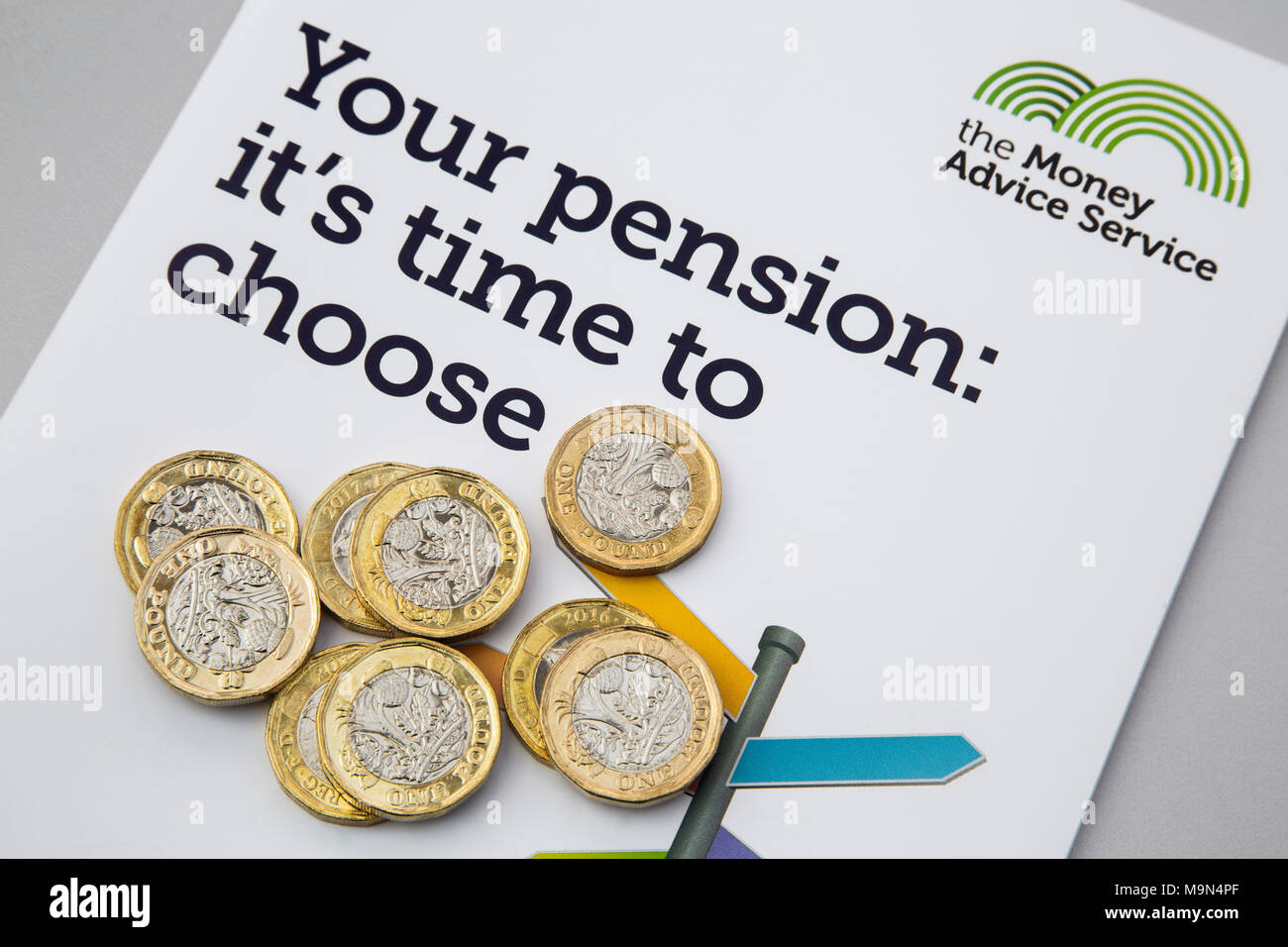 British new pound coins Sterling pounds GBP on a Money Advice Service booklet Your Pension about choosing pensions for retirement. England UK Britain - Stock Image