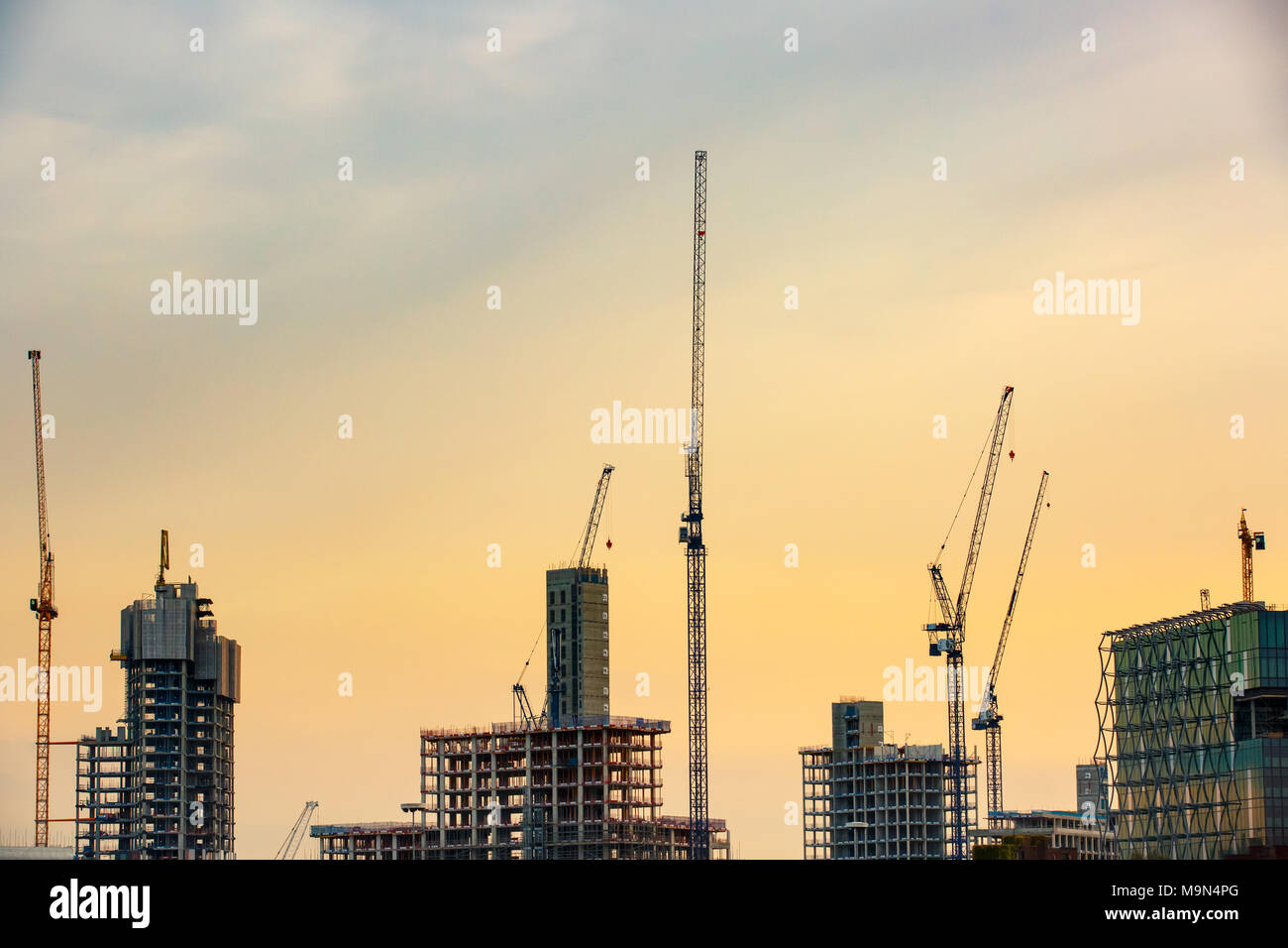 New skyscrapers under construction with tall cranes against yellow sky. Construction business and industry, urbanisation, urban sprawl real estate bub - Stock Image