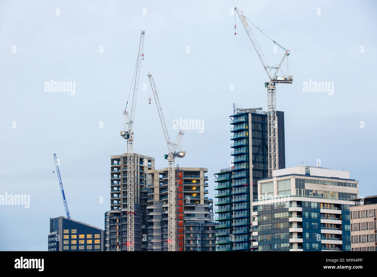 New skyscrapers under construction with tall cranes. Construction business and industry, urbanisation, urban sprawl real estate bubble concept, backgr - Stock Image