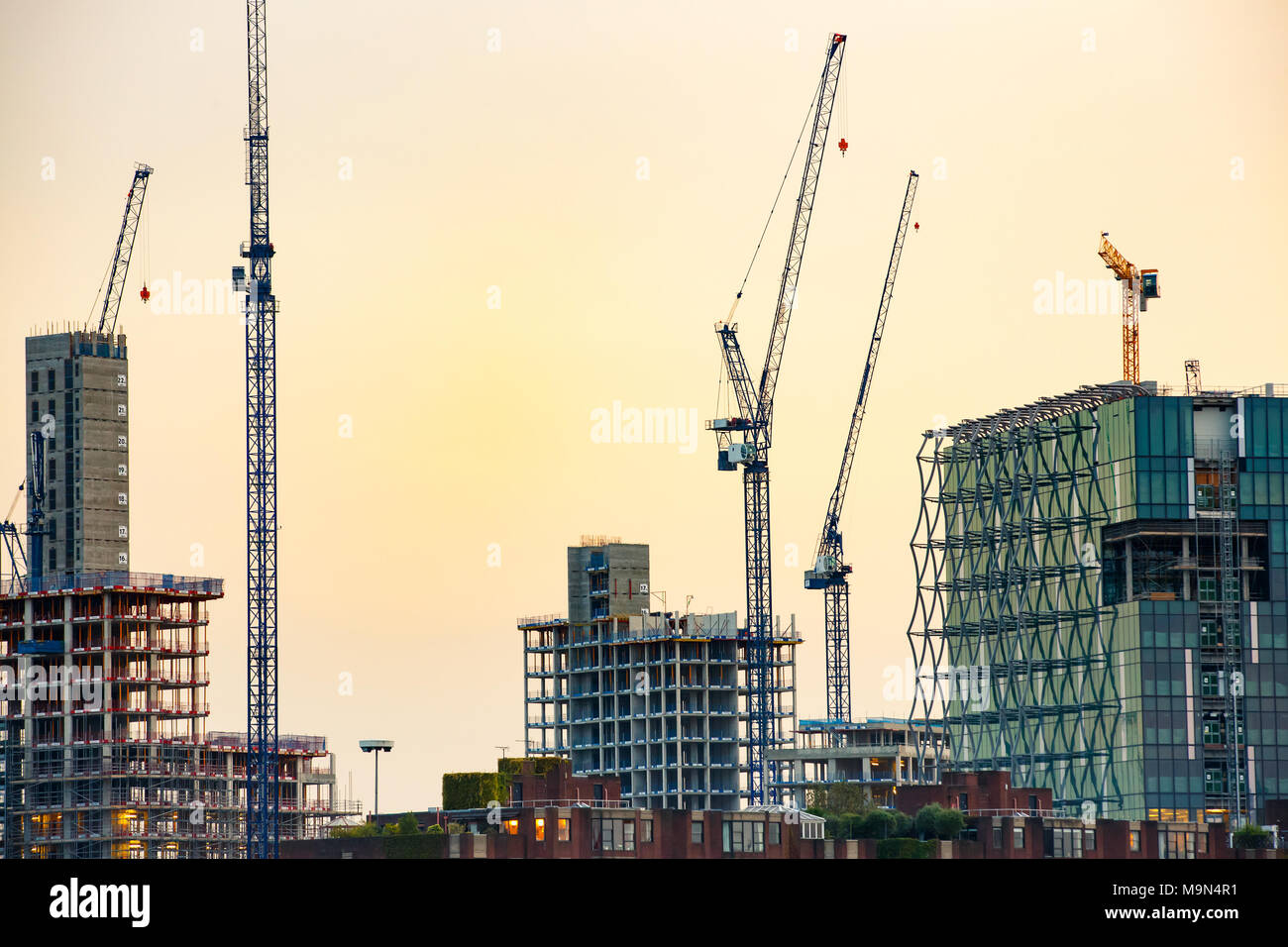New skyscrapers under construction with tall cranes against colourful sky. Construction business and industry, urbanisation, urban sprawl real estate  - Stock Image