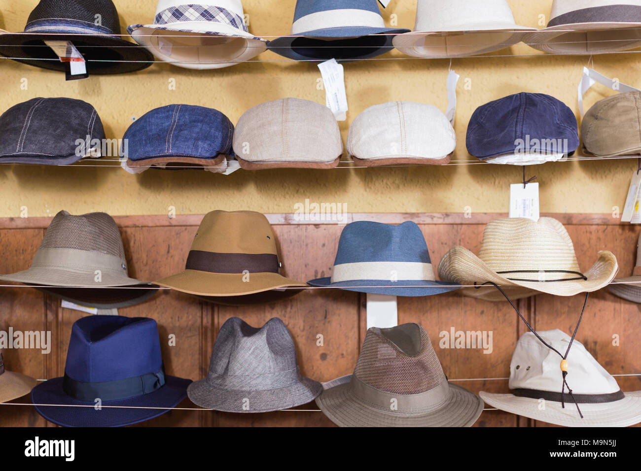23b8b25d3ad1a4 Trendy fedora hats hanging on the wall of country shop - Stock Image