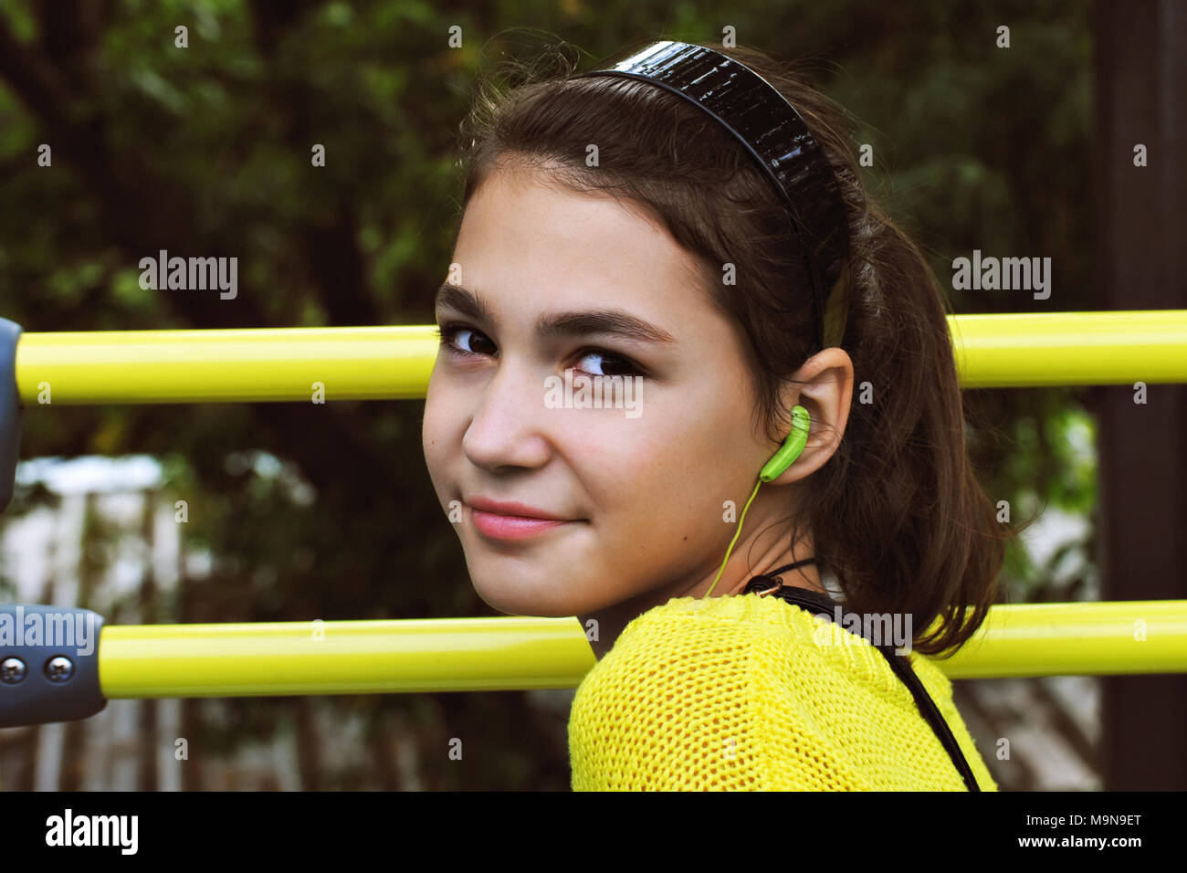 A teenage girl in a yellow sweater listens with headphones to the story of a guide sitting on the top floor of a tour bus in Paris. - Stock Image