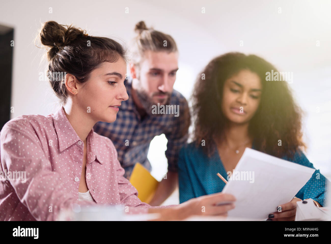 Multiracial business team working together around a laptop   - Stock Image