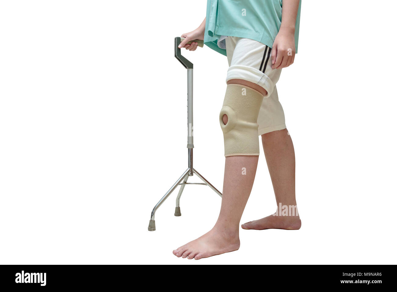 Woman walking on cane , wearing knee support in rehab center - Stock Image