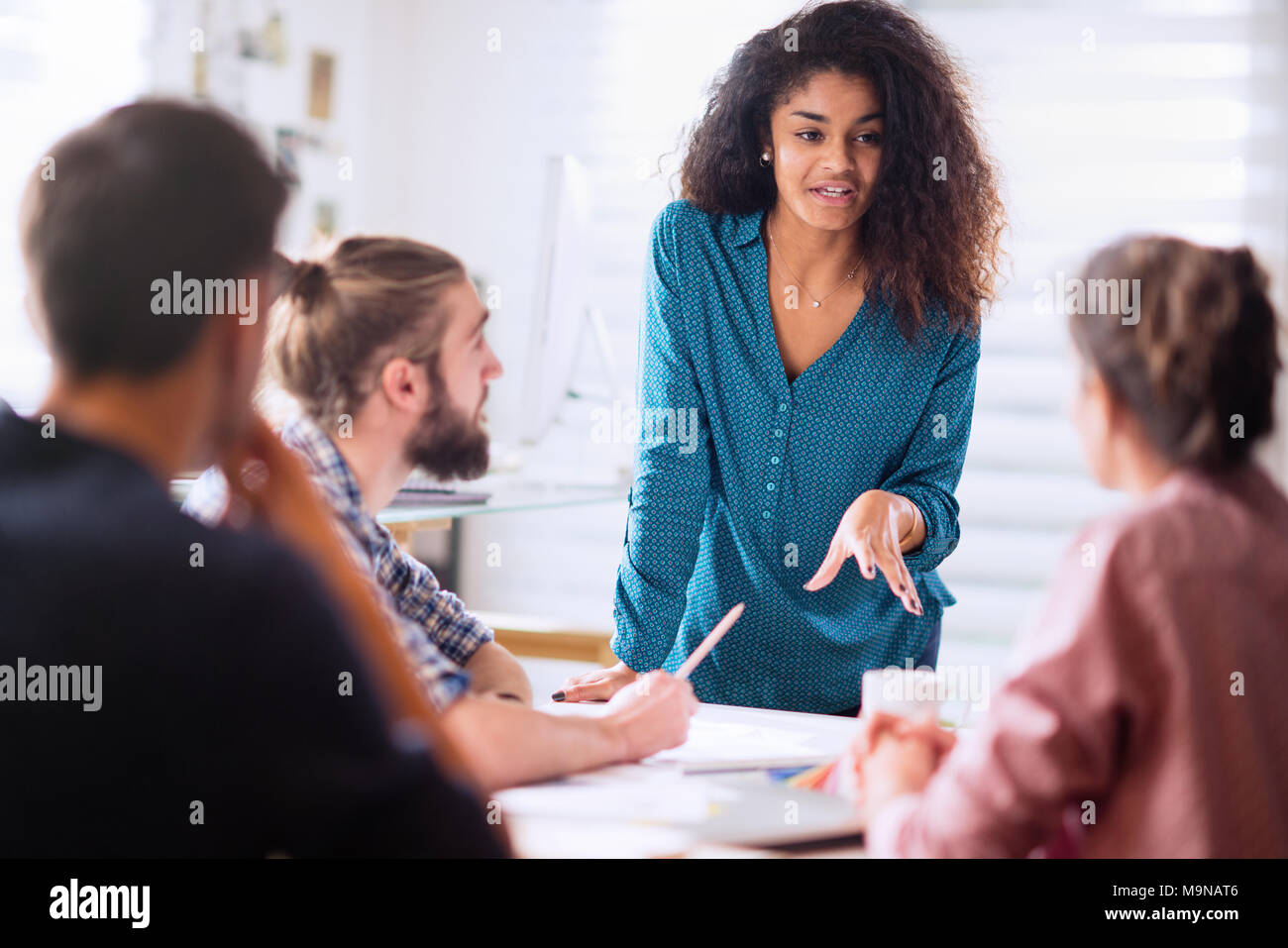 Meeting at office. a black woman discusses with her colleagues  - Stock Image