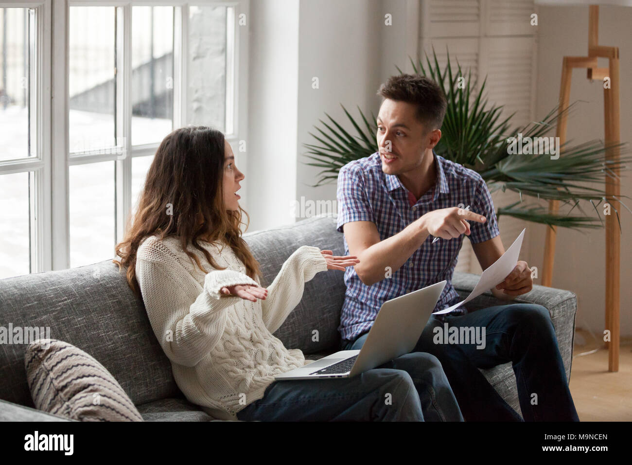 Young couple arguing about high domestic bills to pay with laptop and documents, unhappy family having conflict disagreement discussing unpaid debt or - Stock Image