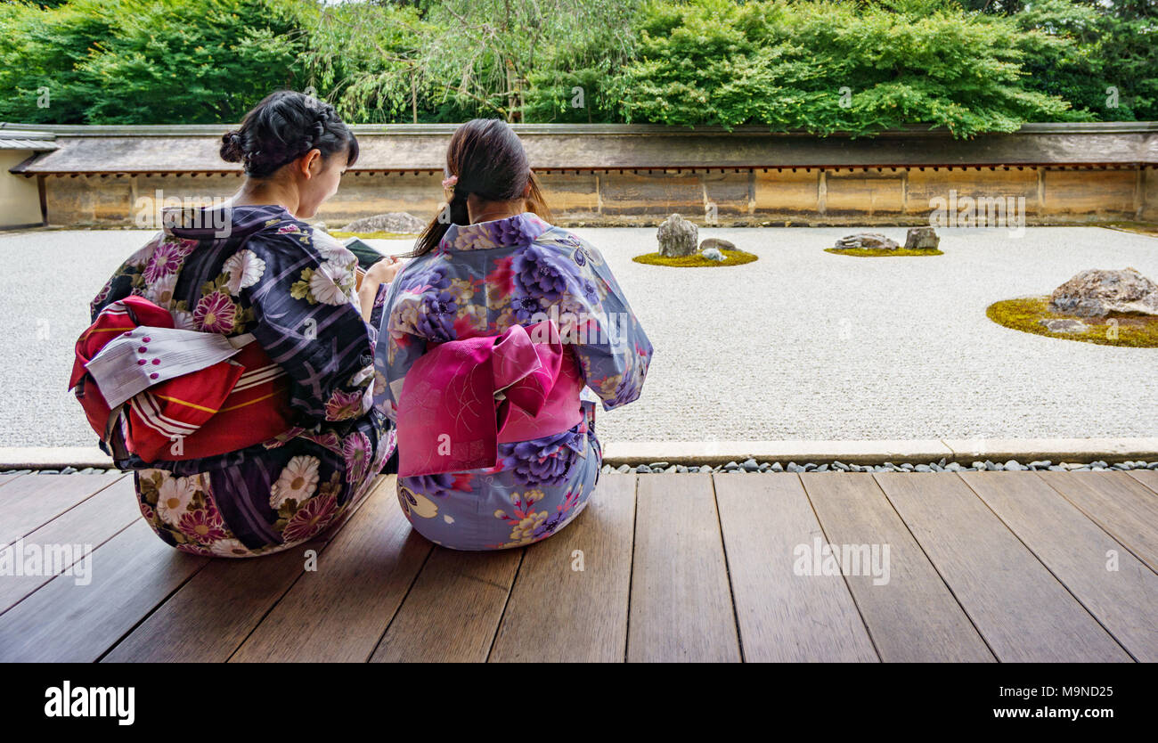 KYOTO, JAPAN - JUNE 7: Unidentified women dress in traditional clothes and observe Japanese typical zen garden in Kyoto on June 7, 2015 in Japan Stock Photo