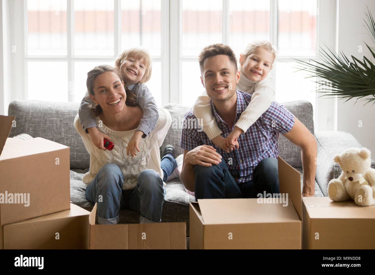 Portrait of happy young multinational family bonding together, smiling adopted kids embracing parents on couch with boxes on moving day, children hugg Stock Photo
