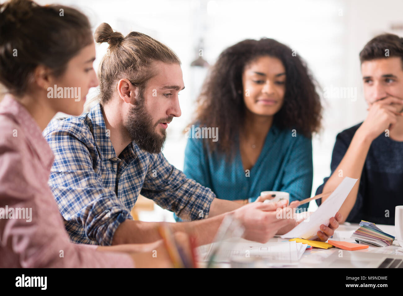 Young multiethnic creative team sharing ideas on a project  - Stock Image