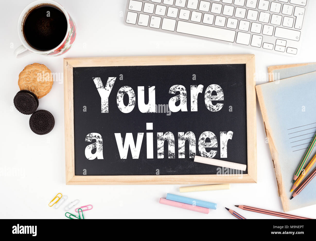 You are a winner. Chalkboard on white office desk - Stock Image