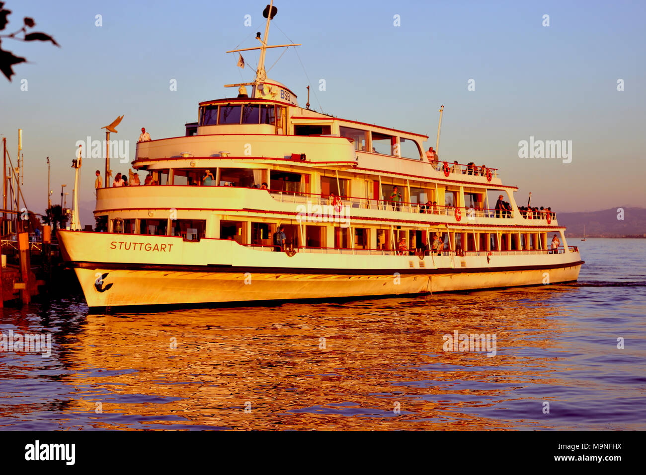 A cruise ship docks in the late evening sunset after taking passengers around Lake Constance, Germany and Switzerland. - Stock Image