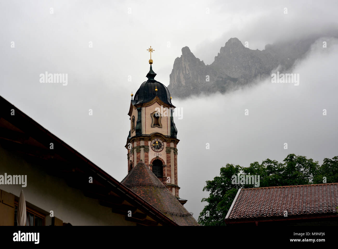 On an overcast, rainy summer day, the peaks of the Zugspitze German Alps peak through rain clouds behind Mittenwald's 1746 church steeple. - Stock Image