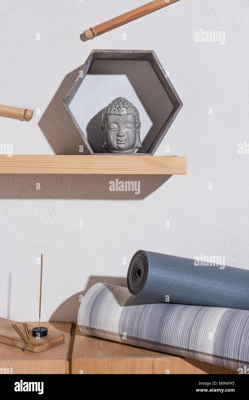 sculpture of buddha head in frame and yoga mats with incense sticks Stock Photo