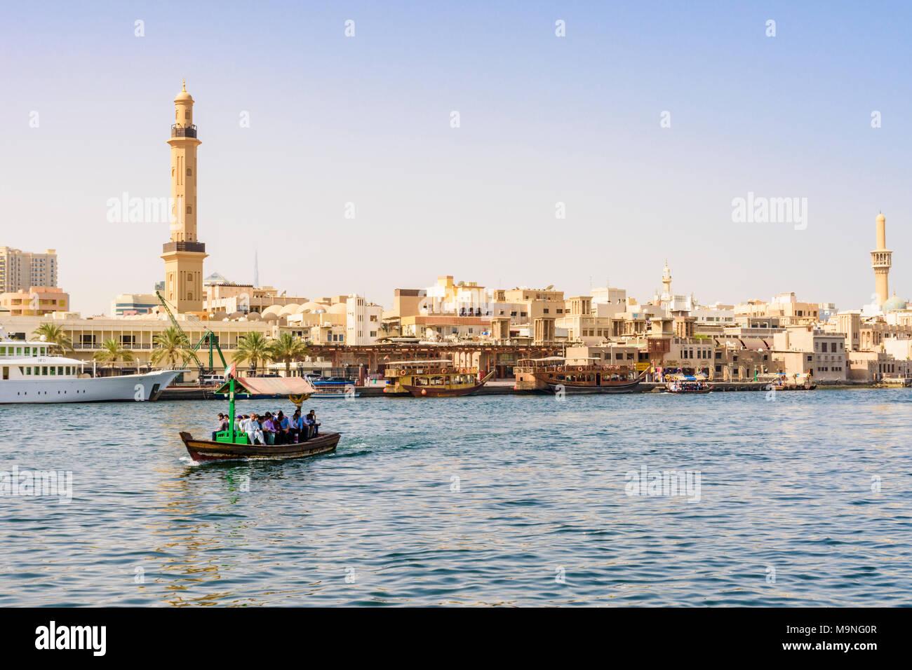 Dubai Creek abra boat with views over to the Grand Mosque Minaret, Dubai Creek, Dubai, UAE - Stock Image