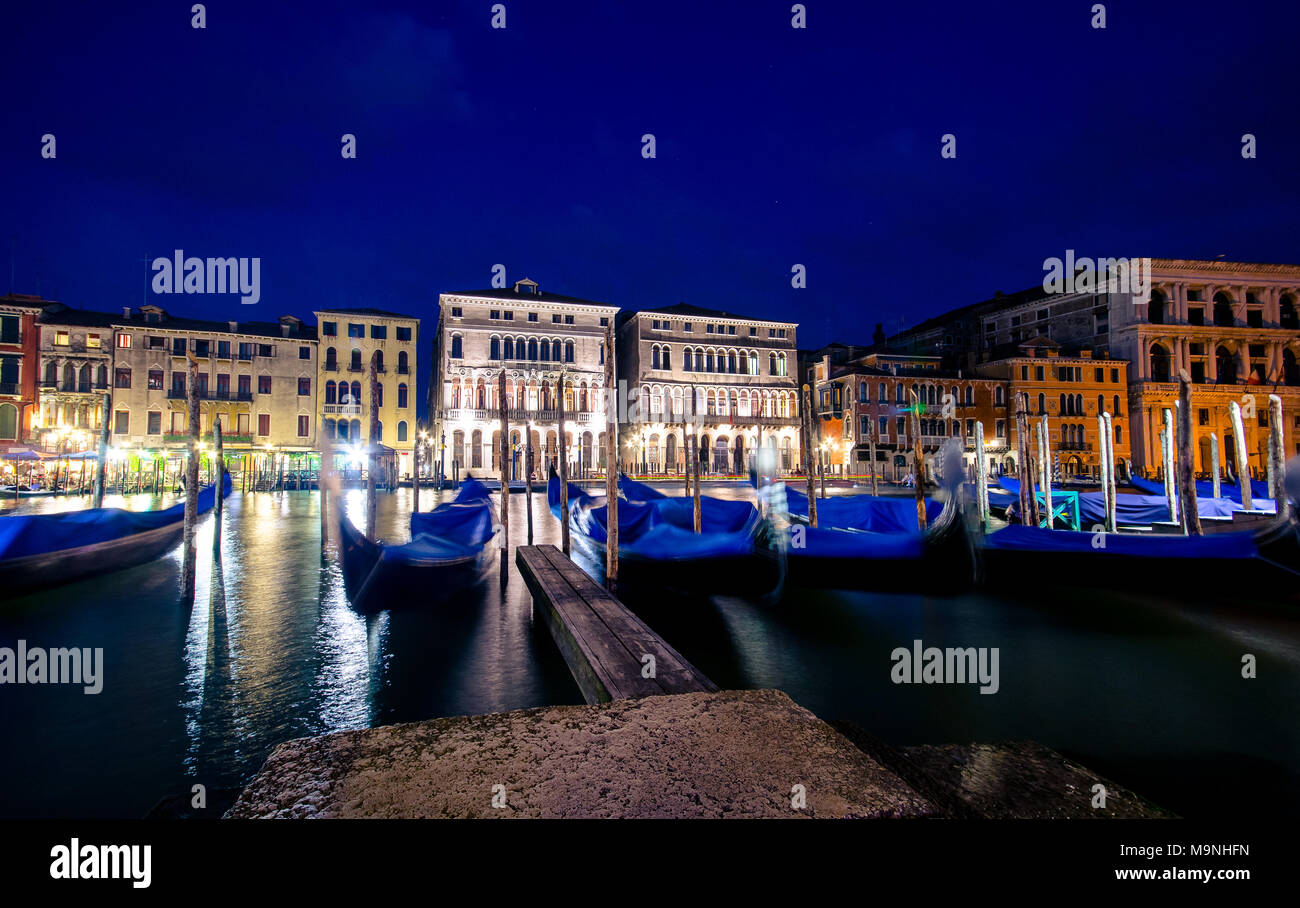 Italy Venice grand canal gondola pier row anchored overnight at sunset blurred illuminated at poles from sea water along ancient palaces - Stock Image