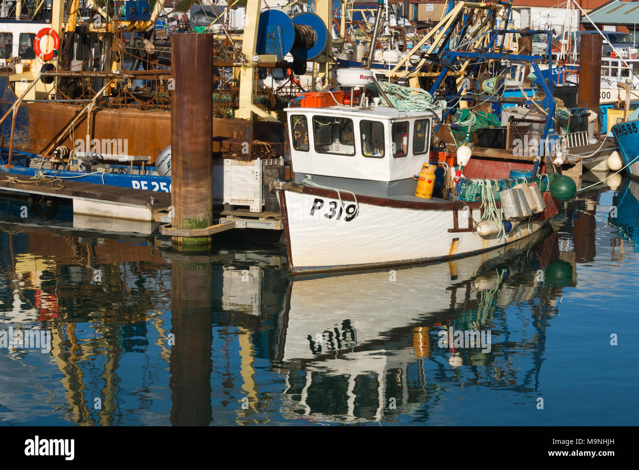 Fishing boats and their reflections while at their moorings in Camber Dock by Spice Island in Old Portsmouth, Portsmouth, on a calm day Stock Photo