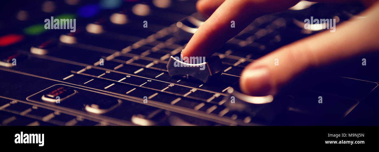 Cropped hand of audio engineer operating sound mixer - Stock Image