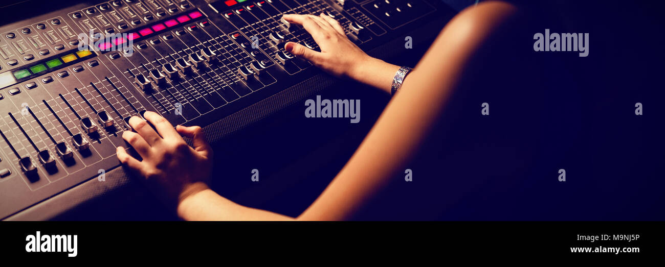 Female audio engineer using sound mixer Stock Photo