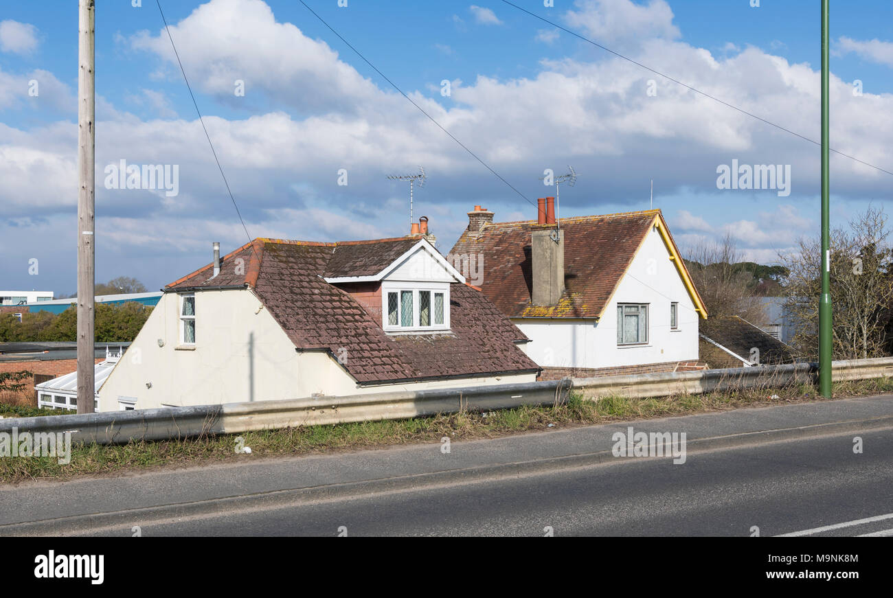 House roof showing where a home is built below the level of a road, where the road goes over a bridge in England, UK. - Stock Image