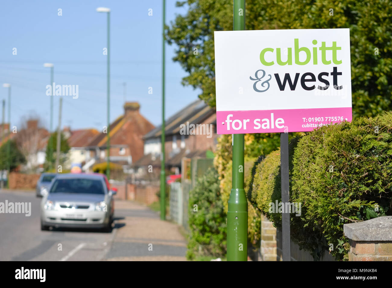 Cubitt & West estate agents 'For Sale' sign outside a house in the UK. - Stock Image