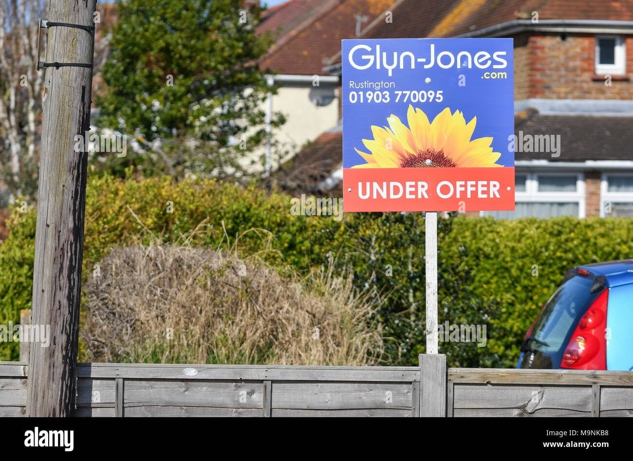 Glyn-Jones estate agents 'under offer' sign outside a house in the UK. Selling house. Selling home. - Stock Image