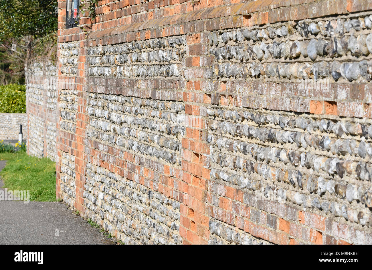 Old flint stone wall with bricks in the UK. - Stock Image