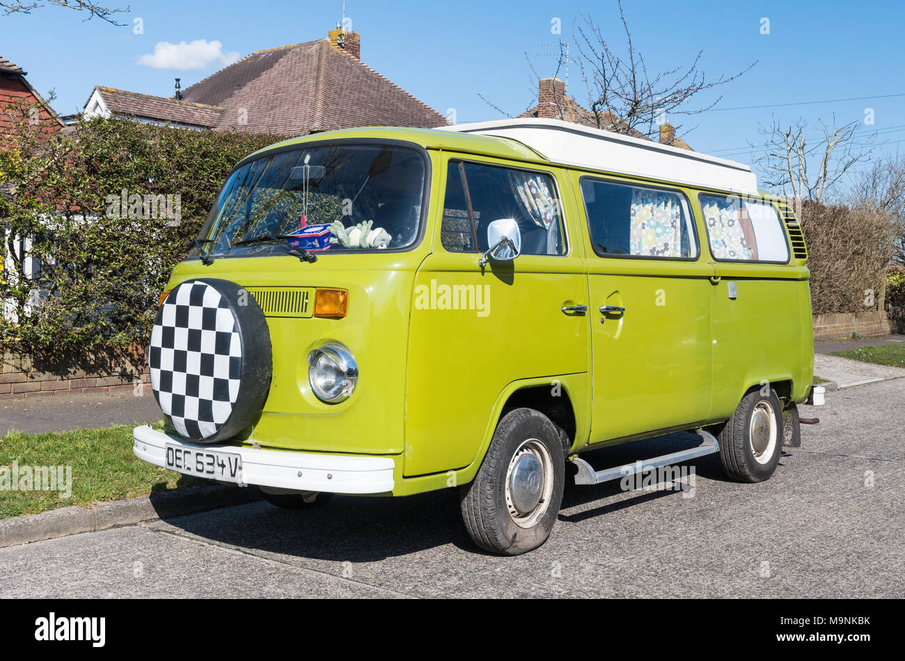 Volkswagen Camper Van (car) Type 2 (T2 or T2b) with a hard top built in 1979 in green, parked on a roadside in the UK. - Stock Image