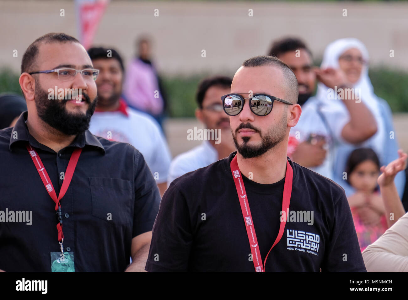 A young Arab event organizer (event security) wearing sunglasses at Event in Umm Al Emirat Park, Abu Dhabi, UAE Stock Photo