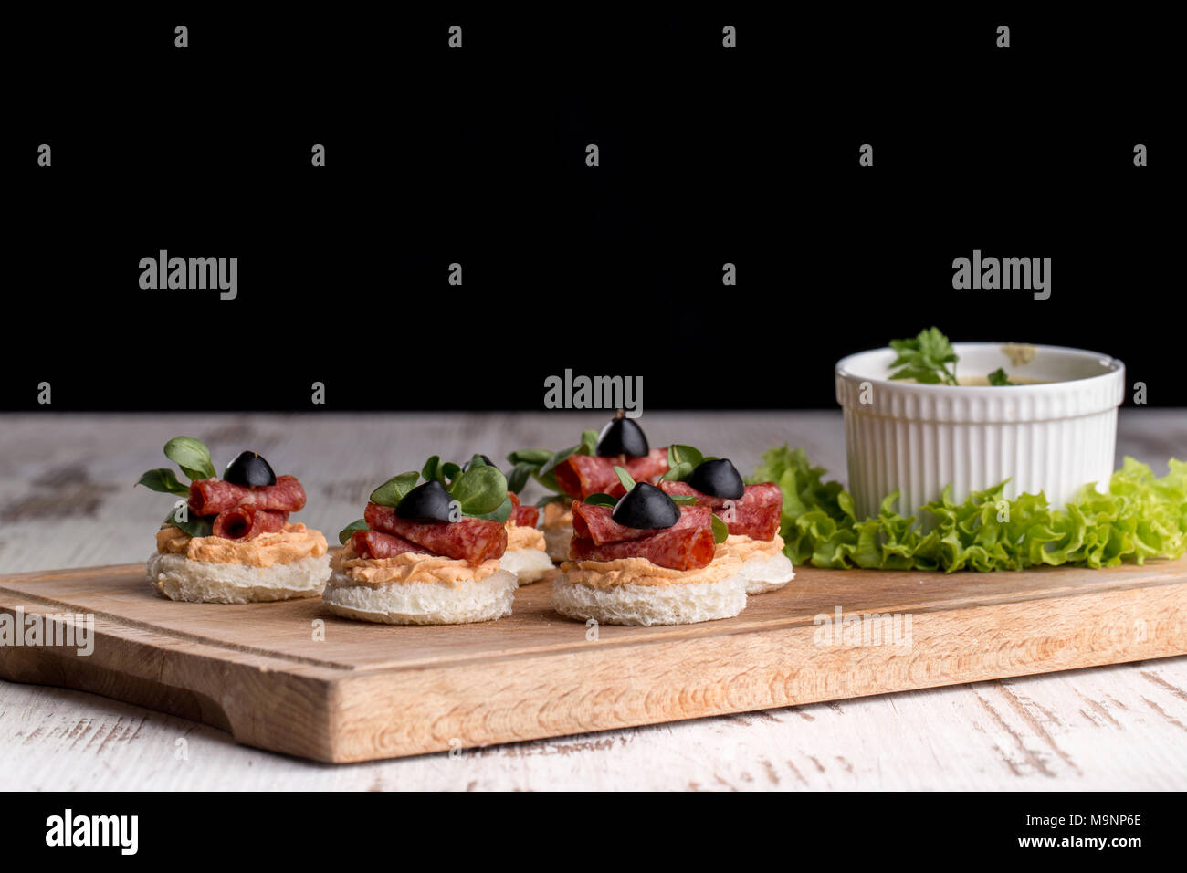 Delicious canapes with salami, olives and spices on a woody background - Stock Image