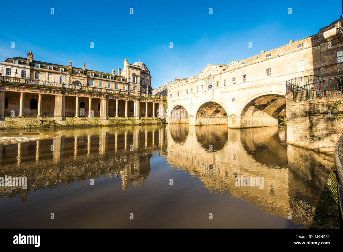 Historic Pulteney Bridge's three arches and the Grand Parade columns reflected in the  shimmering River Avon in Bath with a beautiful clear blue sky - Stock Image