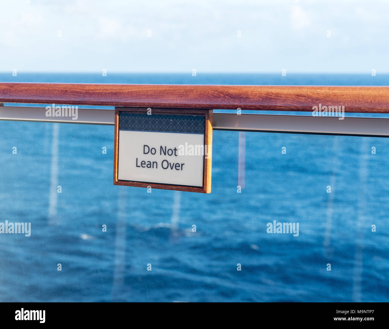 Do Not Lean Over warning sign on railing of cruise ship - Stock Image