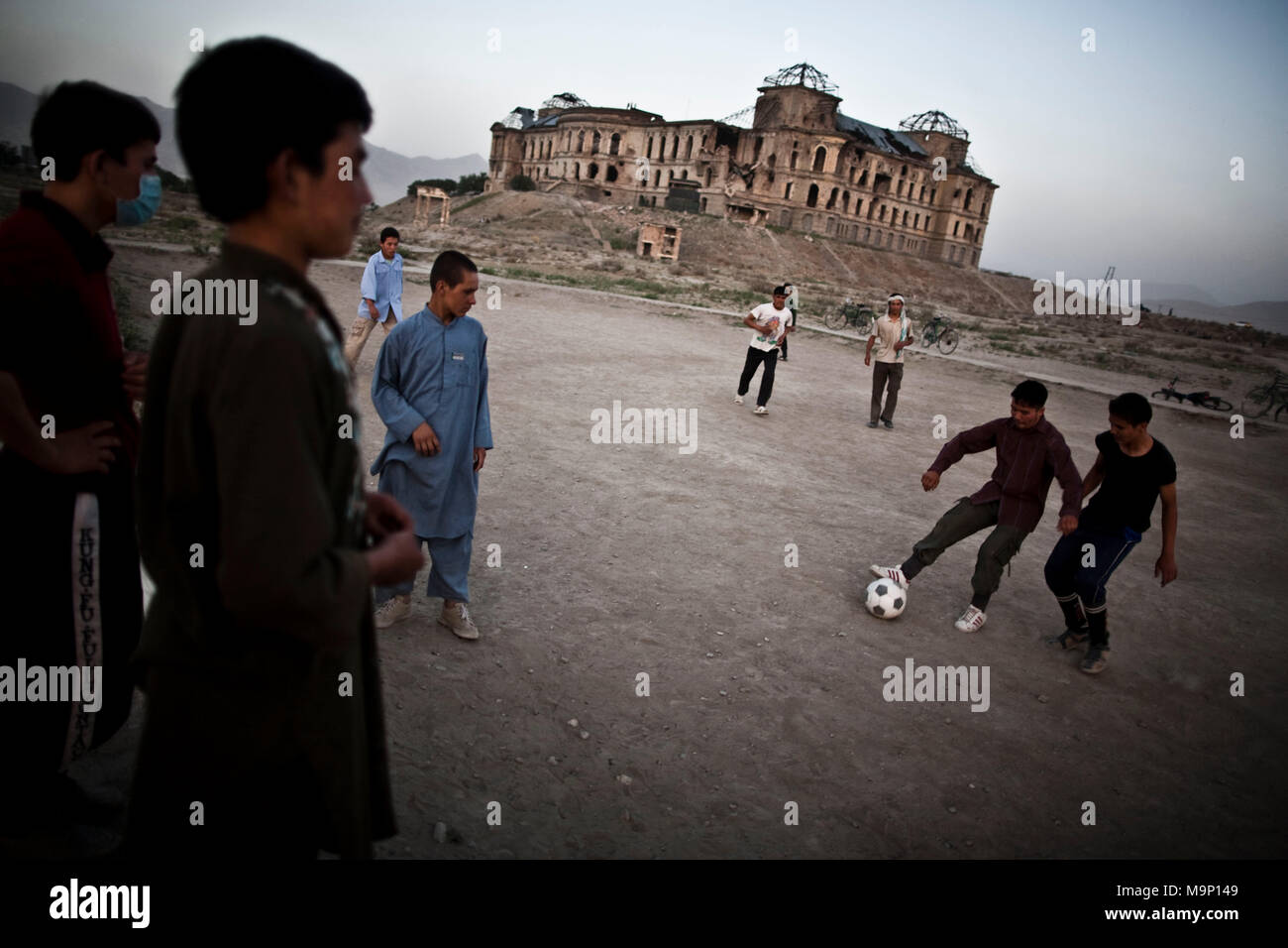 Afghan boys play soccer as the bombed out Darul Aman Palace which stands for 'abode of peace,' destroyed during the civil war in Kabul, Afghanistan, Wednesday, July 15, 2009. - Stock Image