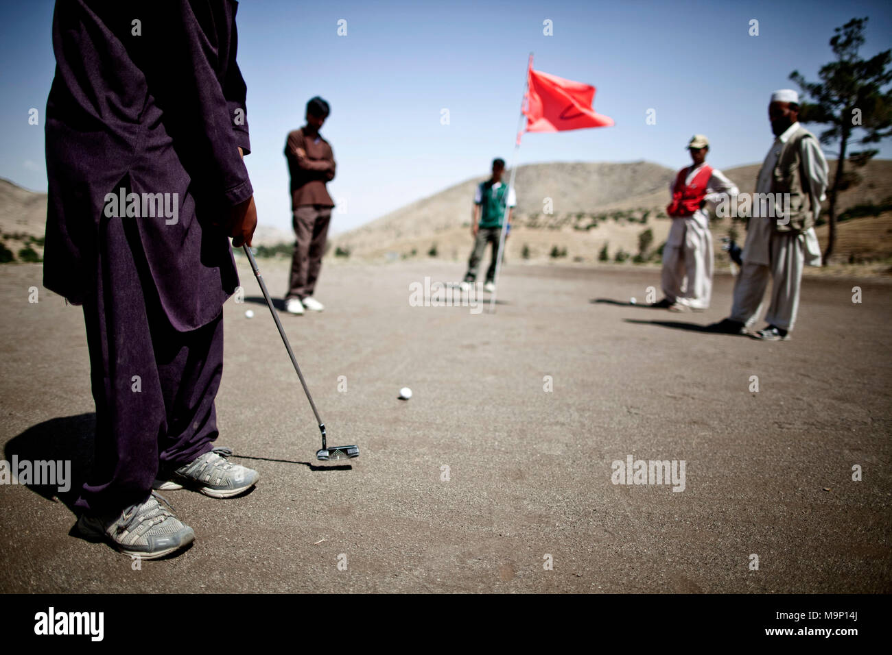 An Afghan golfers putts on the 2nd hole at the Kabul Golf Club in Kabul, Afghanistan, July 17, 2009. This is the only golf course in Kabul and it reopened in 2003. - Stock Image