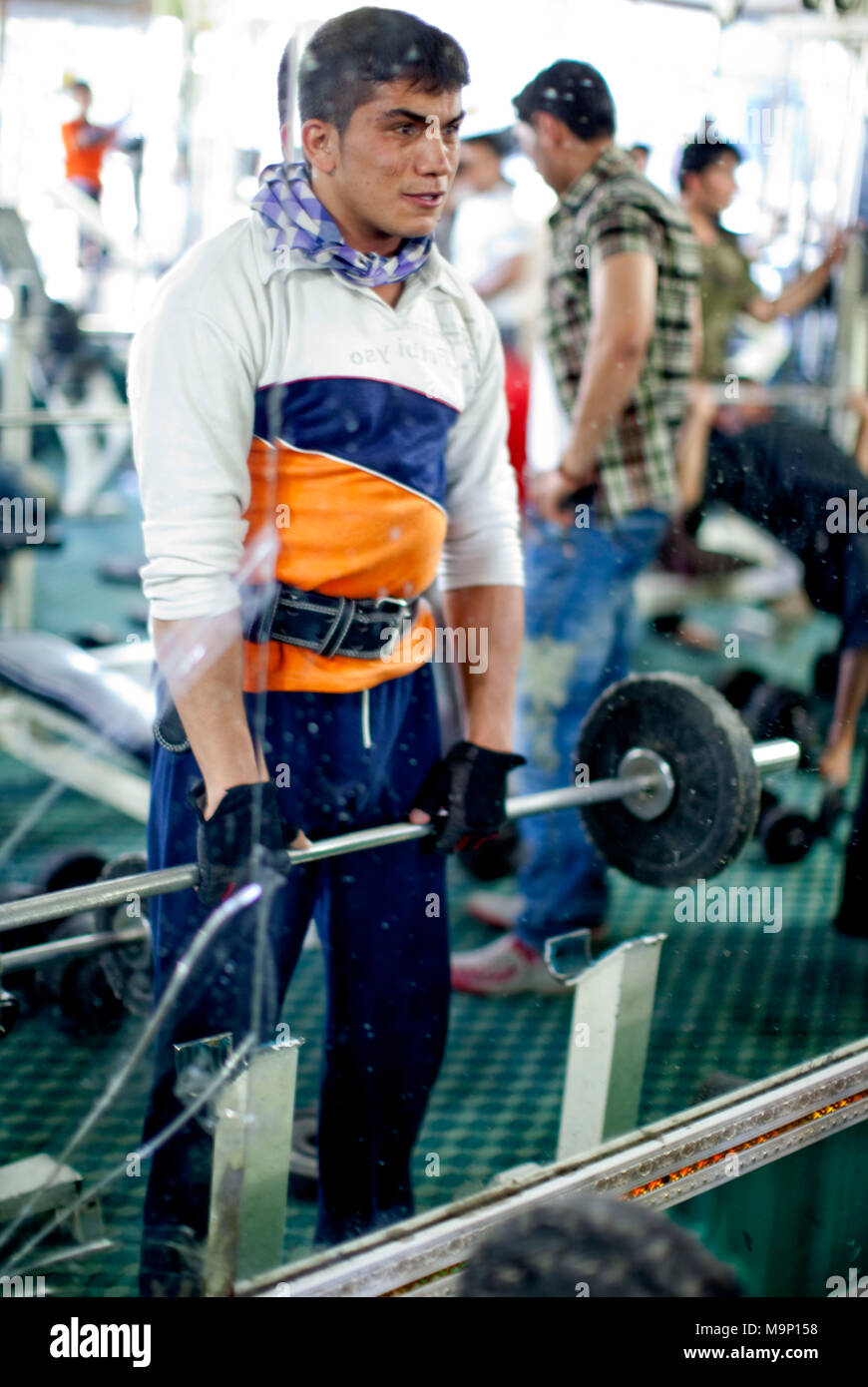 An Afghan man exercises at Gold's Gym in Kabul, Afghanistan, Friday, July 17, 2009. This is the first weight lifting facility to open after the fall of the Taliban. - Stock Image