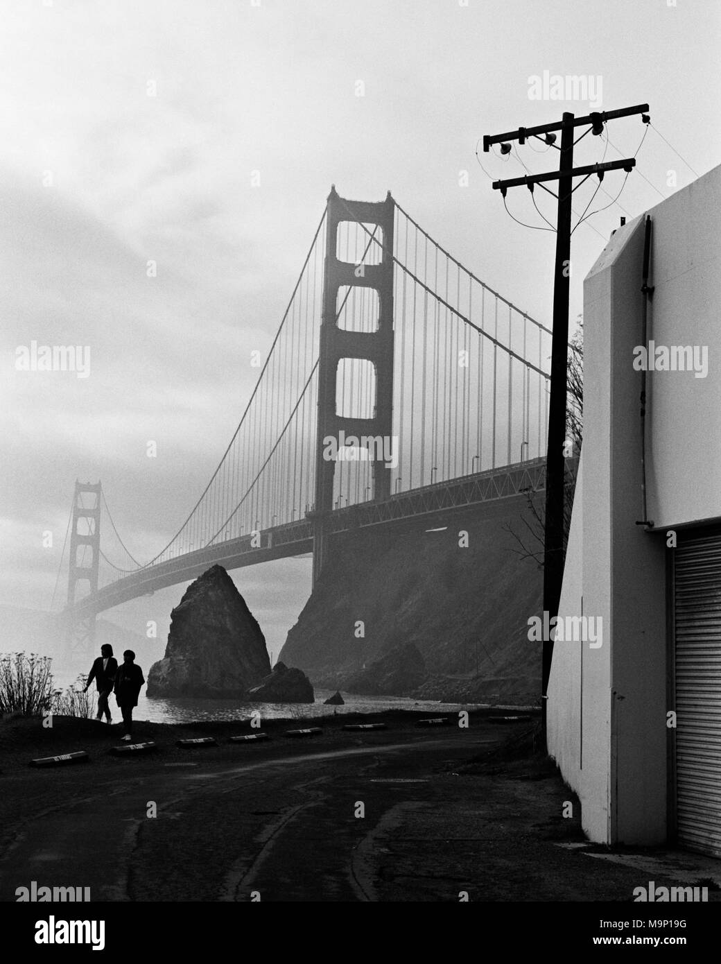 A silhouetted couple walking along the water with the Golden Gate Bridge in the background. Golden Gate National Recreation Area, Marin County, California. Stock Photo