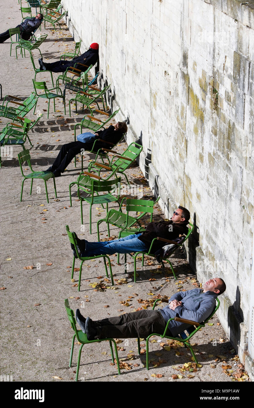 Parisians sunning themselves in the park on a cold autumn day in Paris. - Stock Image