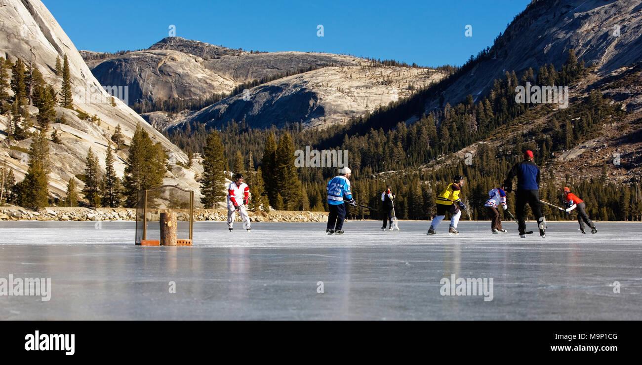 People playing ice hockey on a frozen, snow free Tenaya Lake in Yosemite National Park. - Stock Image