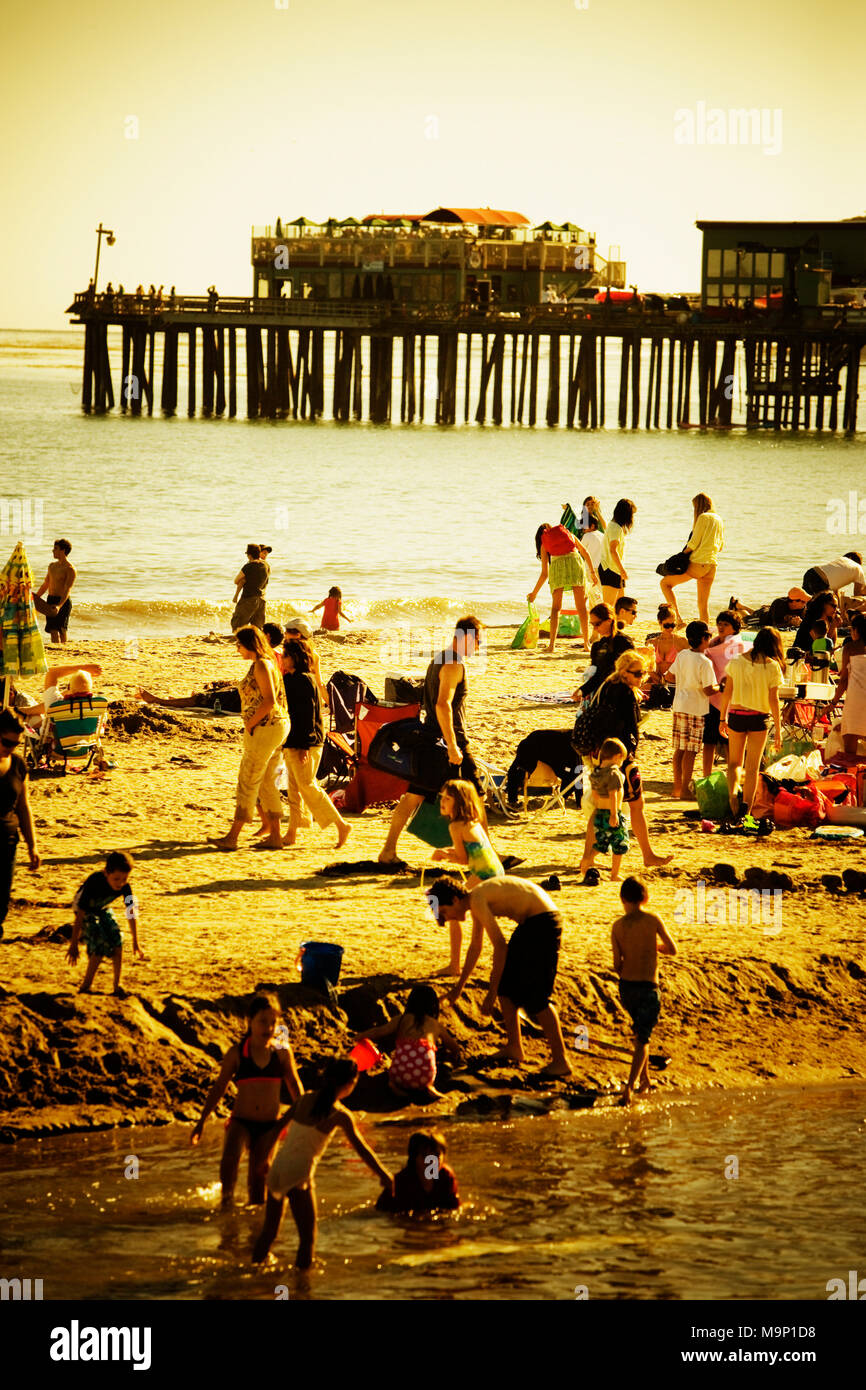 People at play on the beach in Capitola. Sepia and yellow toned. - Stock Image