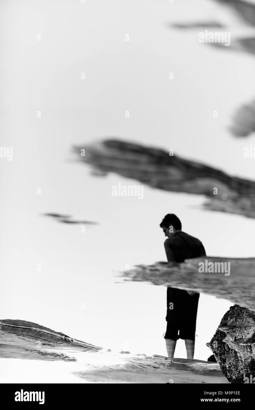 A woman reflected in the water of a sandy beach along the Oregon coast. - Stock Image