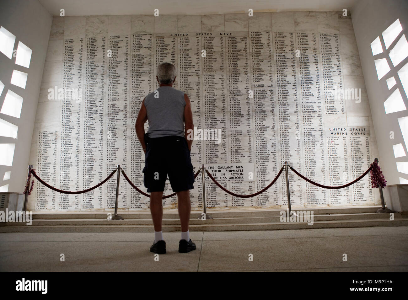 Rear view of a man standing in the shrine room, where the names of those killed on the USS Arizona are engraved on the marble wall. The USS Arizona Memorial at Pearl Harbor, Honolulu, Hawaii is final resting place for many of the ship's 1,177 crewmen who lost their lives on December 7, 1941. - Stock Image